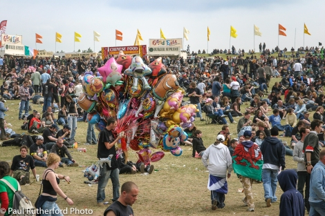 A balloon seller eating a hot-dog, while walking among the crowd, in the main arena at Download Festival